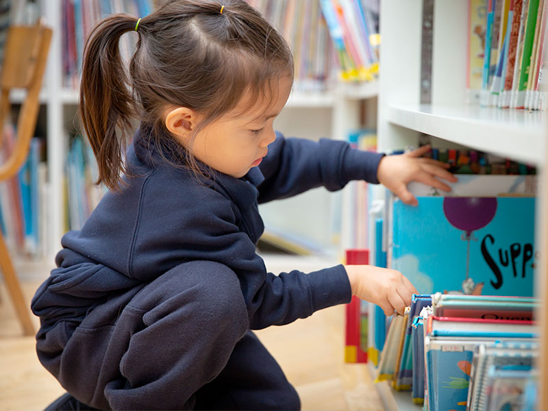 Child choosing a book from the book shelf