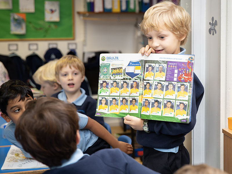 Boy showing football collection to class